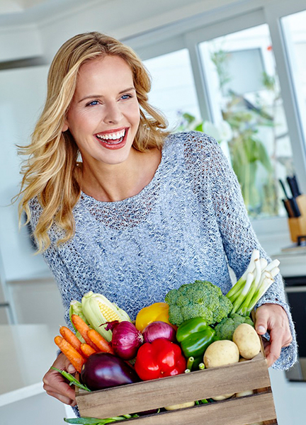 Healthy woman holding basket of vegetables