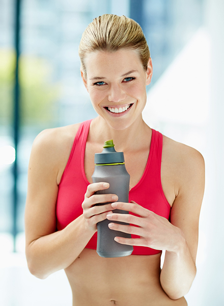 Cropped portrait of an attractive young woman drinking water after a workout